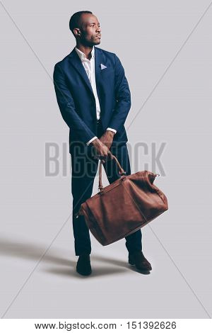 Complementing his style with bag. Full length of handsome young African man in full suit carrying brown leather bag and looking away while standing against grey background
