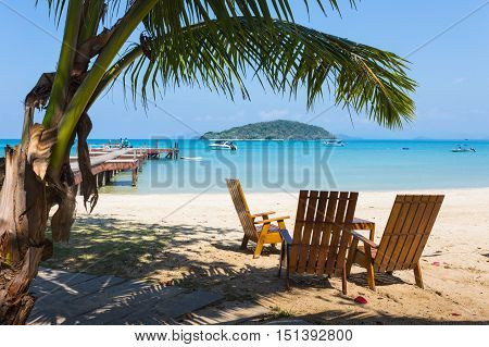 Tropical Beach Panorama With Deckchairs, Boats And Palm Tree