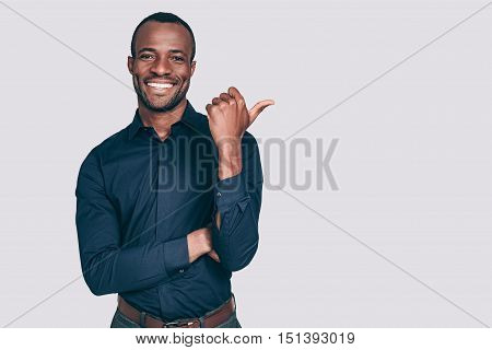 Look over there! Handsome young African man pointing away and smiling to you while standing against grey background