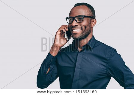 Good talk. Handsome young African man talking on smart phone and smiling while standing against grey background