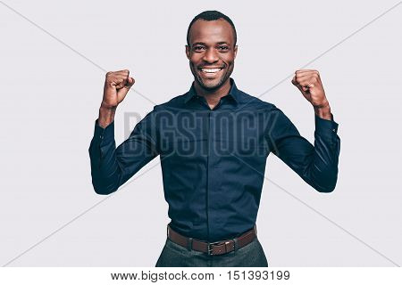 Everyday winner. Happy young African man gesturing and looking at camera with smile while standing against grey background