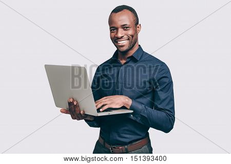 How may I help you? Handsome young African man working on laptop and smiling to you while standing against grey background