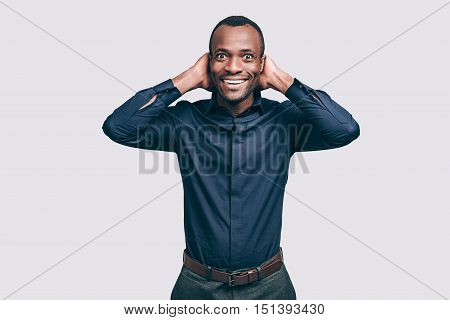 Feeling so happy! Happy young African man holding hands behind head and looking at camera with smile while standing against grey background