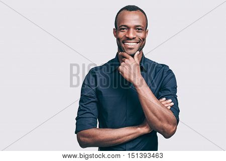 Confident and successful. Handsome young African man holding hand on chin and looking at camera with smile while standing against grey background