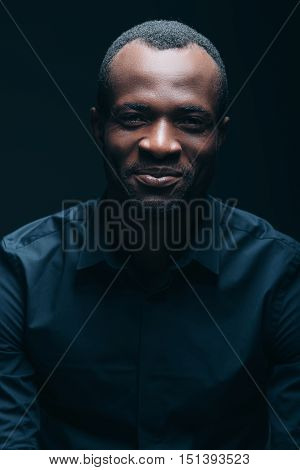 Always stay real! Portrait of handsome young African man looking at camera with smile while being in front of black background