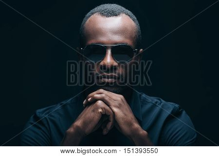 Confident and trendy look. Portrait of handsome young African man leaning his head on hands and looking at camera while being in front of black background