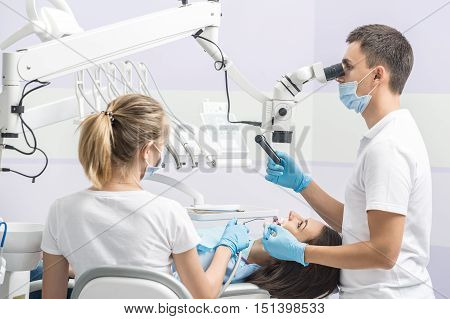 Pretty girl with patient bib on a dental chair and dentist with assistant who sit next to her. Man looks on her teeth using dental microscope and holds a dental mirror. Woman holds air water syringe.