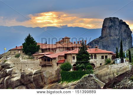 Meteora monasteries. Beautiful view on Monastery of the Holy Trinity placed on the edge of high rock against the beautiful sunset Kastraki Greece