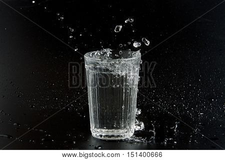 Water is poured into a beaker on a dark background
