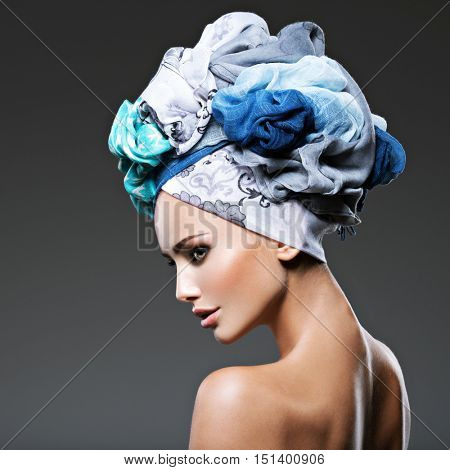 Profile portrait of beautiful  girl  in turban. Creative portrait of fashion woman. Young model posing at studio