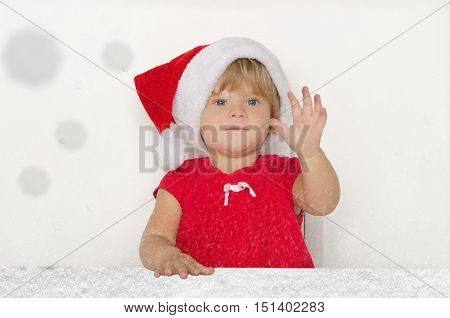 little baby dressed as Santa under the falling snow on gray background