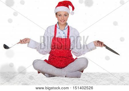 Cook in Santa hat yoga knives and snow on white background