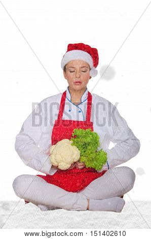 chef in hat of Santa Claus yoga vegetables under snow on white background