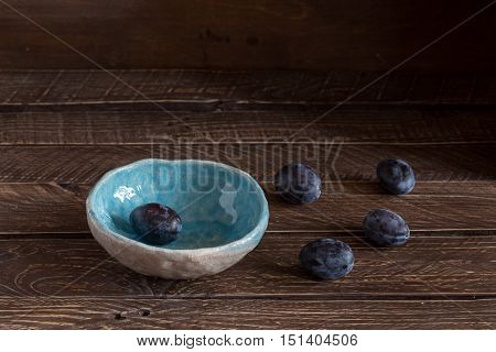blue ceramic bowl with plums plums in a clay bowl plums on a brown background.