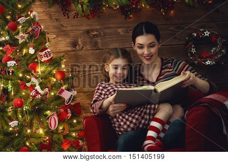 Merry Christmas! Pretty young mother reading a book to her daughter near Christmas tree.