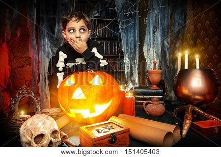 Scary funny boy in a costume of skeleton in a wizarding lair. Halloween party. Halloween decorations.