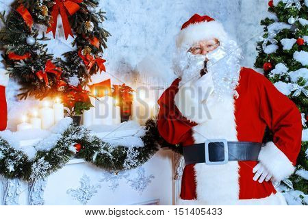 Jolly Santa Claus standing by the fireplace in a room, decorated for Christmas and smoking a pipe.