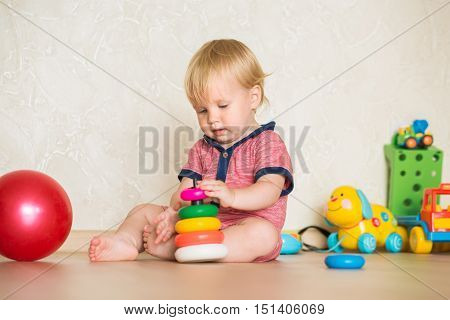 15 year-old child playing with educational cup toys at home. Little blond baby boy with blue eyes is playing with pyramid toy on the floor. Little kid have fun indoors