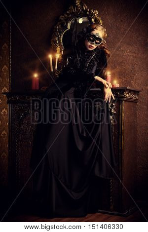 Charming mysterious girl in black mask and black medieval dress stands in a castle living room. Vampire. Halloween concept. Vintage style. poster