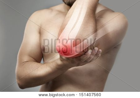 Man with elbow pain on grey background