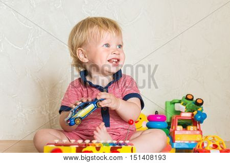 Portrait of a beautiful baby boy on the floor with car toys. 15 month-old child playing with educational cup toys at home. Little blond kid with blue eyes is playing with toy at home indoors