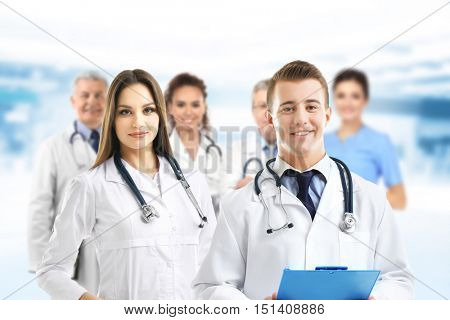 Young doctors and medical team on blurred hospital background. Health care concept.