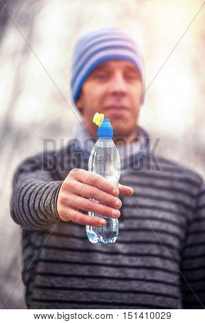 Young Male runner holding water bottle. Witer fitness, running, jogging outdoors.