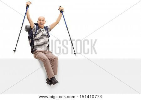 Ecstatic elderly male hiker sitting on a panel isolated on white background