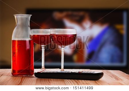 Two glass and carafe of wine with TV remote on light natural wooden table. Concept of romantic movie watching.