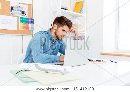 Handsome pensive young businessman working and using laptop in the office