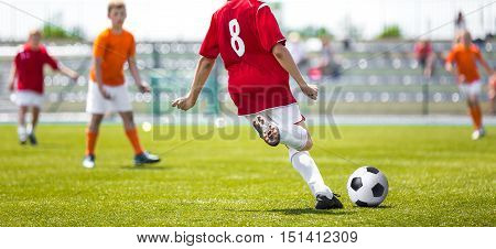 Soccer classes for children. Young soccer football players kicking soccer ball on sports field. International soccer league tournament for youth football teams