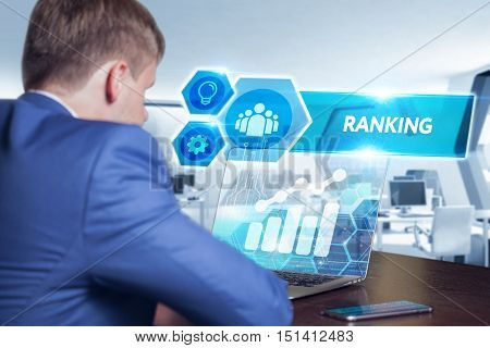 Business technology internet and networking concept. Young businessman working on his laptop in the office select the icon Ranking on the virtual display.