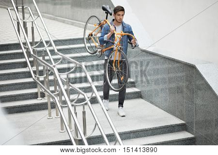 Guy in denim jacket going down the stairs holding an orange bicycle. Student with the bike going down