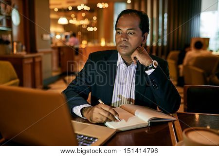 Indian business executive working on laptop in restaurant