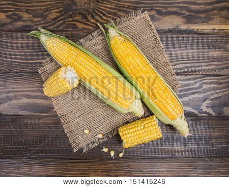 Corn Cobs On A Sackcloth On A Wooden Background