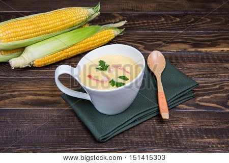 Cup Of Corn Soup And Fresh Corn On The Wooden Table