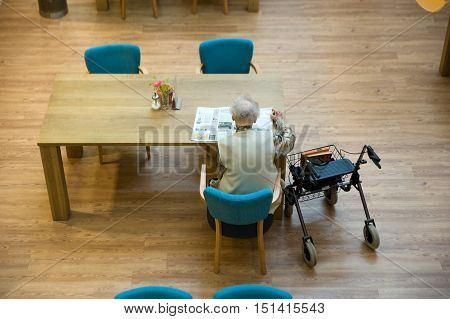 ALMELO THE NETHERLANDS - JUNE 14 2016: An elderly woman is reading a newspaper on the table of an elderly home.