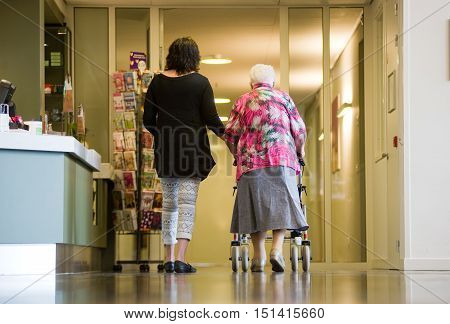 ALMELO THE NETHERLANDS - JUNE 15 2016: A woman is assisting an elderly woman with a rollator in an elderly home.