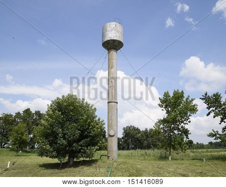 Silver Water Tower Among Green Grass And Trees