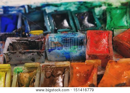 Artists Brushes And Watercolour Paints On Palette. Vintage Stylized Photo Of Paintbrushes Closeup An