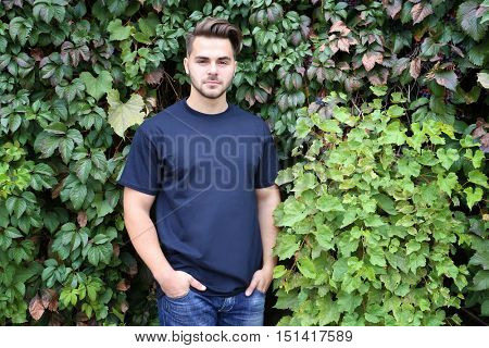 Young man in blank t-shirt on green leaves background
