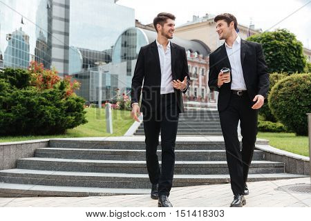 Two happy young businessmen with take away coffee walking and talking outdoors