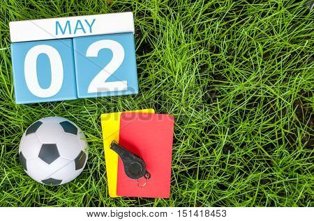 May 2nd. Day 2 of month, calendar on football green grass background. Spring time, empty space for text.