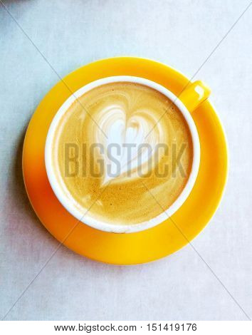 Top view of a heart shaped in a yellow cup of latte cappuccino coffee. Cafe art with milk cofee round ceramic glass and plate for coffe lovers - aka latte art.