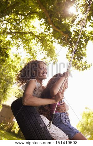 Mother And Daughter Sitting On Tire Swing In Garden