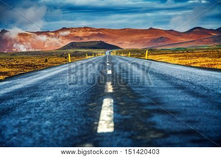 Empty road leading to geothermal area Hverir (Hverarond) near Lake Myvatn. Popular tourist attraction. Dramatic and picturesque scene. Location place Krafla, island Iceland, Europe. Beauty world.
