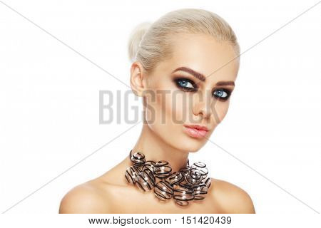 Portrait of young beautiful woman with stylish smoky eye make-up and fancy glass necklace over white background