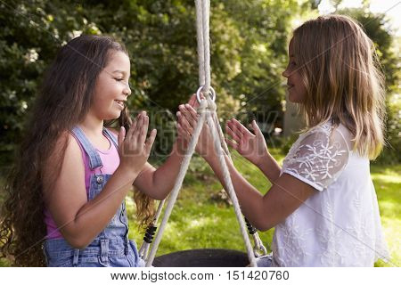 Two Girls Sitting On Swing Playing Clapping Game