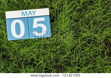 May 5th. Day 5 of month, wooden color calendar on football green grass background. Spring time, empty space for text.