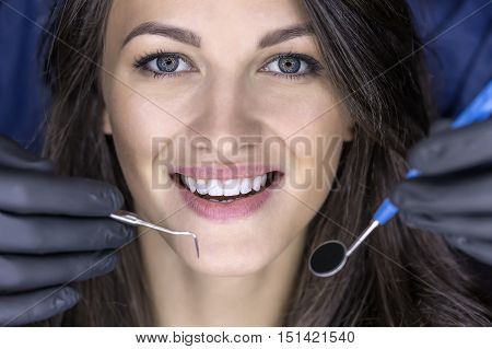Happy girl with a broad smile. There are hands in black medical gloves which holds a dental bur and a dental mirror in front of her face. Macro photo. Horizontal.